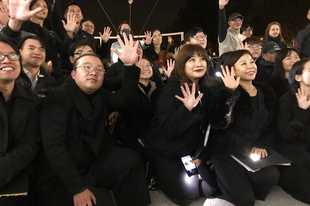 In this Tuesday, Dec. 10, 2019 photo, members of a theater troupe raise their hands to symbolize the five demands of pro-democracy protesters after a performance of Les Miserables in at an outdoor event space in Hong Kong. A Hong Kong theater troupe is making audiences weep by touring a stirring production of 'Les Miserables.' Based on Victor Hugo's tale of rebellion in 19th-century France, the rousing music and lyrics of struggle and resistance struck chords with audience members emotionally and physically drained after six months of protests that have convulsed the city. (AP Photo/John Leicester)