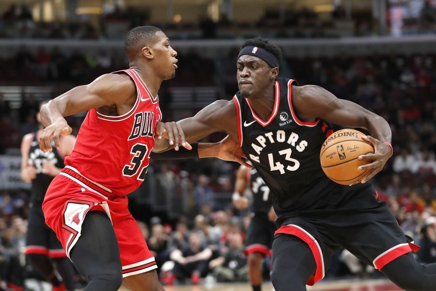 Toronto Raptors' Pascal Siakam, right, drives to the basket as Chicago Bulls' Kris Dunn defends during the first half of an NBA basketball game Monday, Dec. 9, 2019, in Chicago.