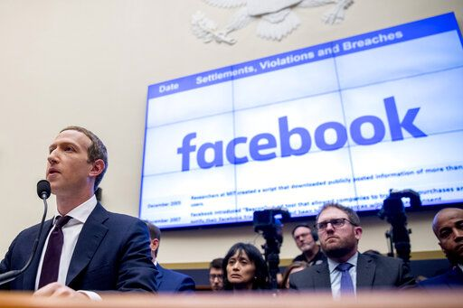 File-This Oct. 23, 2019, file photo shows Facebook CEO Mark Zuckerberg testifying  before a House Financial Services Committee hearing on Capitol Hill in Washington. Facebook's stock dropped almost 3% in regular trading after news reports Thursday, Dec. 12, 2019, suggested that the FTC may take antitrust action to prevent Facebook from integrating its disparate messaging apps. The reports said the Federal Trade Commission may seek a court injunction that would block Facebook's 'œinteroperability'� plans for Facebook Messenger, WhatsApp and Instagram, which involves revising them to use the same underlying software.