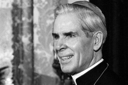 FILE - This Oct. 26, 1966 file photo shows Bishop Fulton J. Sheen in his office at the Propagation of Faith in New York. Sheen, who before his death in 1979 was famous for his radio and TV preaching, had been scheduled to be beatified _ the last step before sainthood _ in a ceremony in Peoria on Dec. 21, 2019. However, the Vatican recently took the rare step of indefinitely postponing the ceremony at the request of the Rochester diocese, which said more time was needed for further investigations.