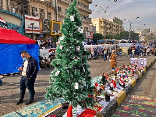 People pass by a Christmas tree with portraits of anti-government protesters who killed under fire from security forces in Tahrir Square during ongoing protests in Baghdad, Iraq, Thursday, Dec. 12, 2019.