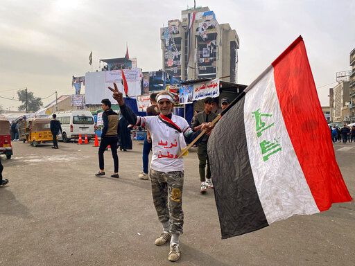 "CORRECTS TO REMOVE REFERENCE TO INCIDENT INVOLVING GUNMAN -  An anti-government protester poses for a picture while holding a national flag during ongoing protests in Baghdad, Iraq, Thursday, Dec. 12, 2019.  The Arabic on his shirt reads, ""We want a homeland."""