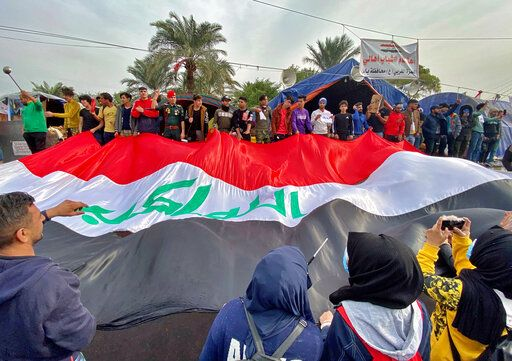 CORRECTS TO REMOVE REFERENCE TO INCIDENT INVOLVING GUNMAN - Anti-government protesters hold a huge Iraqi flag as they gather in Tahrir Square during ongoing protests in Baghdad, Iraq, Thursday, Dec. 12, 2019.