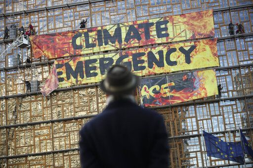 A man looks up as police and fire personnel move in to remove climate activists after they climbed the Europa building during a demonstration outside an EU summit meeting in Brussels, Thursday, Dec. 12, 2019. Greenpeace activists on Thursday scaled the European Union's new headquarters, unfurling a huge banner warning of a climate emergency hours before the bloc's leaders gather for a summit focused on plans to combat global warming.