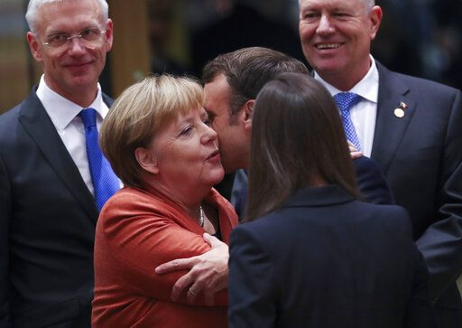 German Chancellor Angela Merkel, second left, is greeted by French President Emmanuel Macron, third right, during a round table meeting at an EU summit in Brussels, Thursday, Dec. 12, 2019. European Union leaders gather for their year-end summit and will discuss climate change funding, the departure of the UK from the bloc and their next 7-year budget.