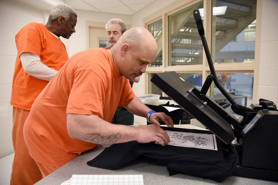 Inmate Marcos Hernandez of Carpentersville aligns his detailed design on a T-shirt in a press at the Kane County jail.