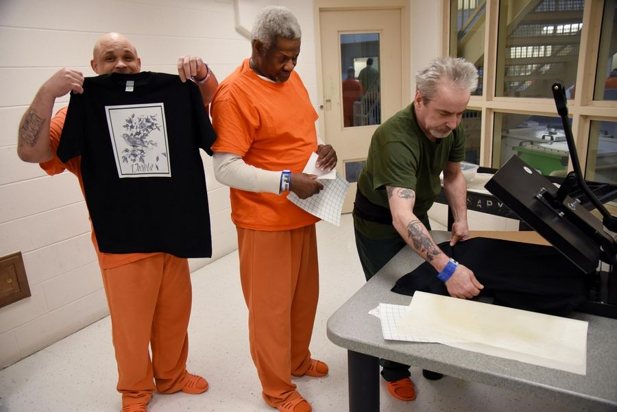 Kane County jail detainee Marcos Hernandez of Carpentersville holds his T-shirt design as John Lundy of Aurora sets a T-shirt in a press and Orlando Riley peels the backing off other artwork.