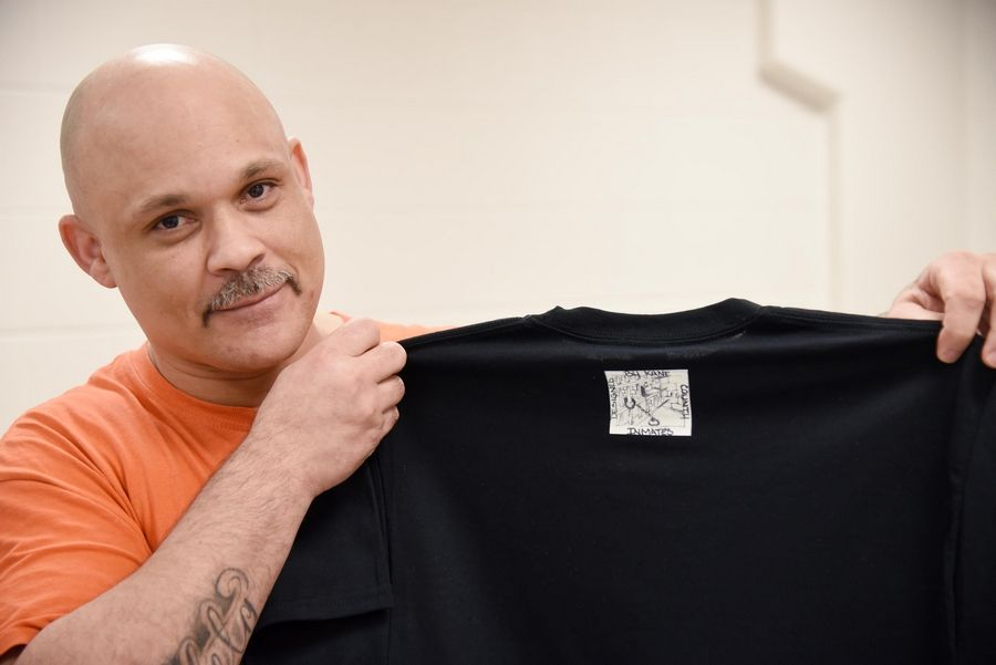 Kane County jail detainee Marcos Hernandez of Carpentersville shows the icon design on the back of a T-shirt. Inmates have designed and are producing T-shirts that they sell on Etsy.