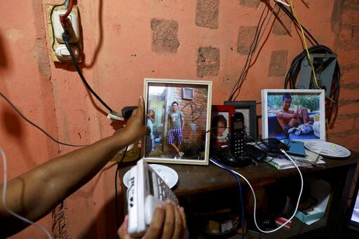 In this Oct. 10, 2019 photo, María Teresa Carballo, shows a picture of her grandson Antony inside of her house in Santa Ana, El Salvador. On a stormy night in 2010, her 17-year-old grandson, Antony, disappeared after being lured from home by a classmate who said there was a girl who wanted to meet him. The classmate was joining a gang and Antony, a resident of the rival gang's territory, was his ticket in. Antony's body was discovered two years later in a septic pit.