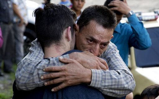 In this Oct. 9, 2019 photo, a father hugs his son outside the Migrant Assistance Office in San Salvador, El Salvador. Buses with deported Salvadorans, such as the son, arrive every day from the U.S. and Mexico.