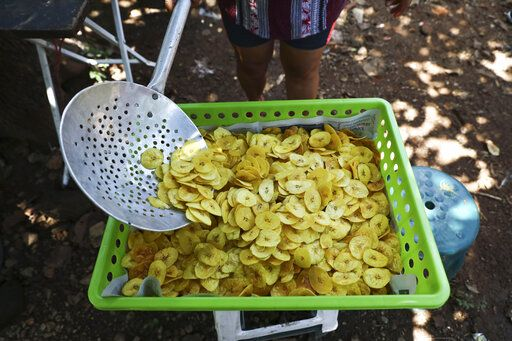 In this Oct. 10, 2019 photo, María Teresa Carballo fries plantain chips outside of her house in Santa Ana, El Salvador. Like much of Central America's massive migration of recent years, the driving force behind the Carballo family's exodus has been fear. Carballo lives in a neighborhood controlled by one gang, but every morning at 5 a.m. she travels to the city's central market, which is controlled by another gang, to buy yucca, plantains and potatoes to make the fried chips she sells for a living.