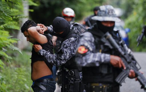 In this Oct. 10, 2019 photo, police frisk a man as part of a routine patrol in Lourdes, La Libertad, El Salvador. El Salvador has seen murders drop dramatically since President Nayib Bukele took office June 1.