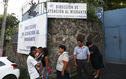 In this Oct. 9, 2019 photo, people gather outside the Migrant Assistance Office in San Salvador, El Salvador. The Trump administration struck a series of agreements with El Salvador, Guatemala and Honduras to stem the flow of migrants at the southern border. Under those pacts, immigrants who pass through those countries on the way to the U.S. are effectively barred from seeking asylum in America.