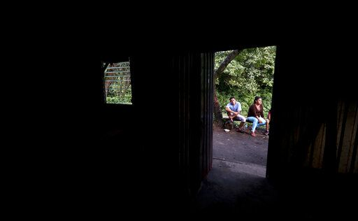 In this Oct. 12, 2019 photo, members of a family sit outside their makeshift house, after being threatened by gangs in Oratorio de Concepcion, El Salvador. The family had to leave their home, carrying only what they were wearing and taking refuge in this place.