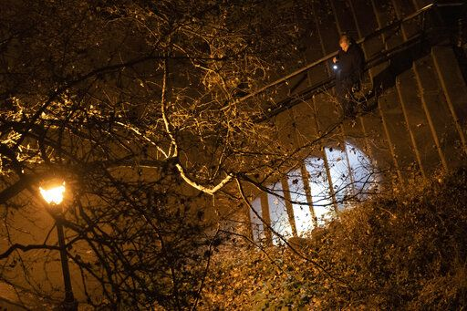 A New York City police department detective use a flashlight to look for evidence in Morningside Park, Thursday, Dec. 12, 2019, in the Upper West Side of Manhattan. Tessa Majors, a 18-year-old Barnard College freshman from Virginia, was fatally stabbed in the park near the school's campus in New York City.