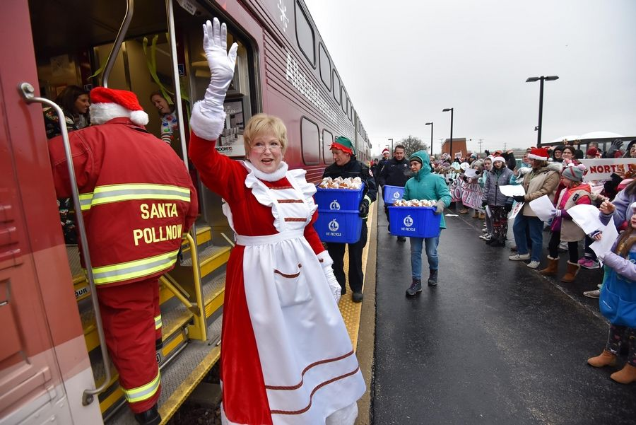 "Mrs. Claus waves to the crowd of 200 as the North Pole Express Metra train stops Saturday morning at the Pingree Road Metra station in Crystal Lake. About 75 families of sick children, along with their nurses, therapy dogs, firefighters and police officers made the round-trip ride from Des Plaines. Tom ""Santa"" Pollnow, a retired Crystal Lake firefighter, wears his red uniform as he enters the train with others to hand out gifts."
