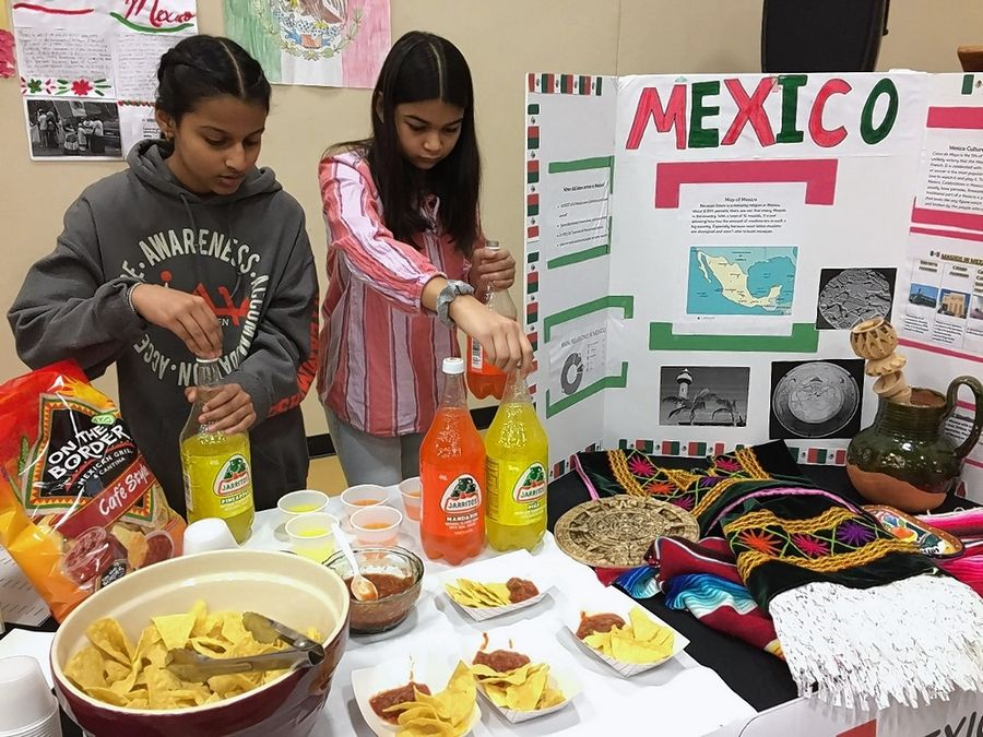 Aasiya Shah and Zohra Hussain, both 13, pour drinks at a booth Saturday at the Islamic Center of Naperville displaying facts about Muslims in Mexico. The country has roughly 12 mosques where Muslims worship, students at the Islamic Center's Al-Falah Academy weekend school found in their research for the third annual Muslims Around the World event.