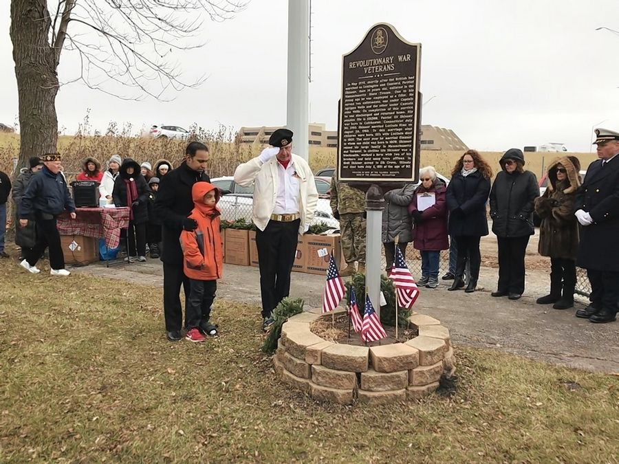 U.S. Rep. Raja Krishnamoorthi and one of his sons accompany Lee Miller, a member of the Elk Grove Village VFW Post 9284, as he lays the first wreath to honor veterans and first responders Saturday during a Wreaths Across America ceremony hosted by the Daughters of the American Revolution.