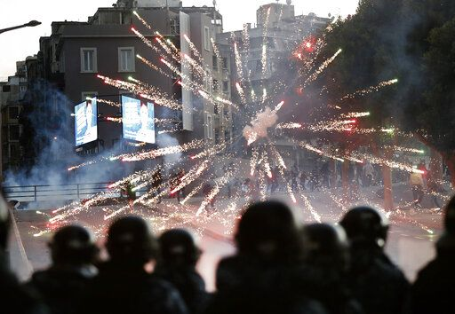 Supporters of the Shiite Hezbollah and Amal Movement groups, background, fire firecrackers against the riot policemen, foreground, as they try to attack the anti-government protesters squares, in downtown Beirut, Lebanon, Saturday, Dec. 14, 2019. Lebanon has been facing its worst economic crisis in decades, amid nationwide protests that began on Oct. 17 against the ruling political class which demonstrators accuse of mismanagement and corruption.