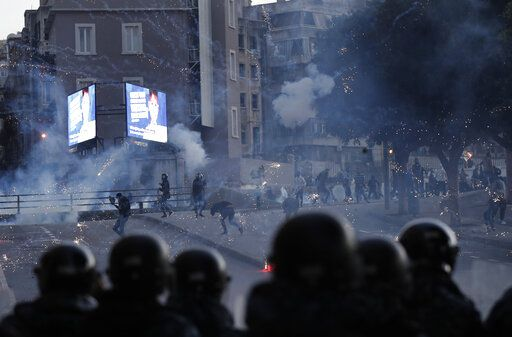 Supporters of the Shiite Hezbollah and Amal Movement groups, background, clashes with the riot policemen, foreground, as they trying to attack the anti-government protesters squares, in downtown Beirut, Lebanon, Saturday, Dec. 14, 2019. Lebanon has been facing its worst economic crisis in decades, amid nationwide protests that began on Oct.17 against the ruling political class which demonstrators accuse of mismanagement and corruption.