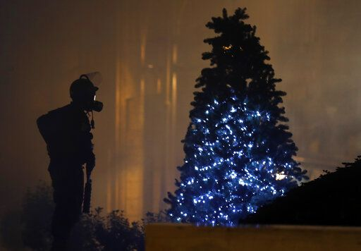 A riot police officer stands next of a Christmas tree during a protest where some anti-government protesters try to enter parliament square in downtown Beirut, Lebanon, Saturday, Dec. 14, 2019. The recent clashes marked some of the worst in the capital since demonstrations began two months ago. The rise in tensions comes as politicians have failed to agree on forming a new government.