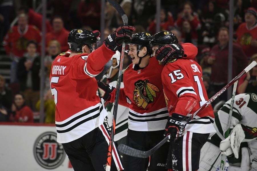 Blackhawks' David Kampf center, celebrates with teammates Zack Smith (15) and Connor Murphy (5) after scoring a goal during the second period of an NHL hockey game against the Minnesota Wild, Sunday, Dec. 15, 2019, in Chicago.