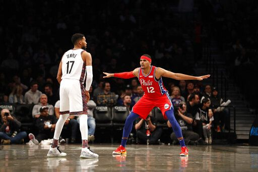 Philadelphia 76ers forward Tobias Harris (12) defends against Brooklyn Nets guard Garrett Temple (17) during the third quarter of an NBA basketball game at Barclays Center, Sunday, Dec. 15, 2019, in New York.
