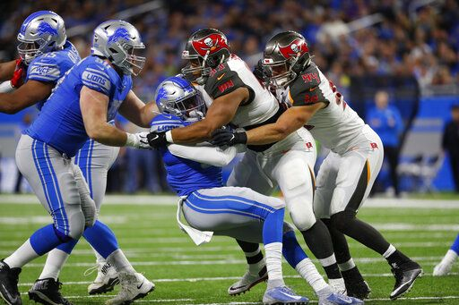 Detroit Lions running back Wes Hills is tackled by Tampa Bay Buccaneers nose tackle Ndamukong Suh (93) and linebacker Carl Nassib during the first half of an NFL football game, Sunday, Dec. 15, 2019, in Detroit.