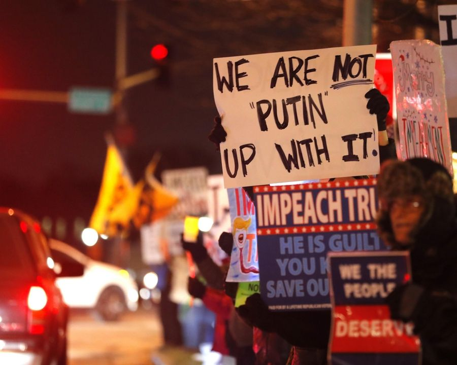 "Activists gather Tuesday evening at Arlington Heights Road and Northwest Highway as part of the nationwide ""Nobody Is Above the Law"" rallies on the eve of the House of Representatives' vote on impeachment."