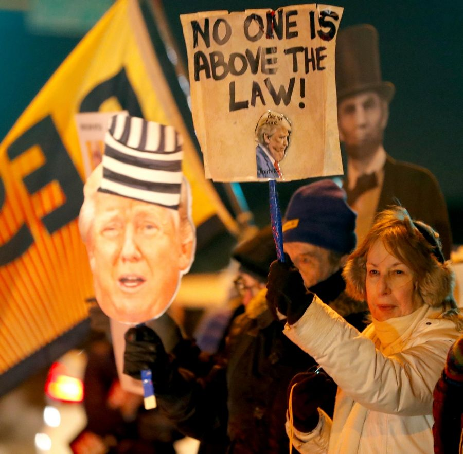 "Gayle Weiss of Arlington Heights hoists a sign as activists gather Tuesday evening at Arlington Heights Road and Northwest Highway as part of the nationwide ""Nobody Is Above the Law"" rallies on the eve of the House of Representatives' vote on impeachment."