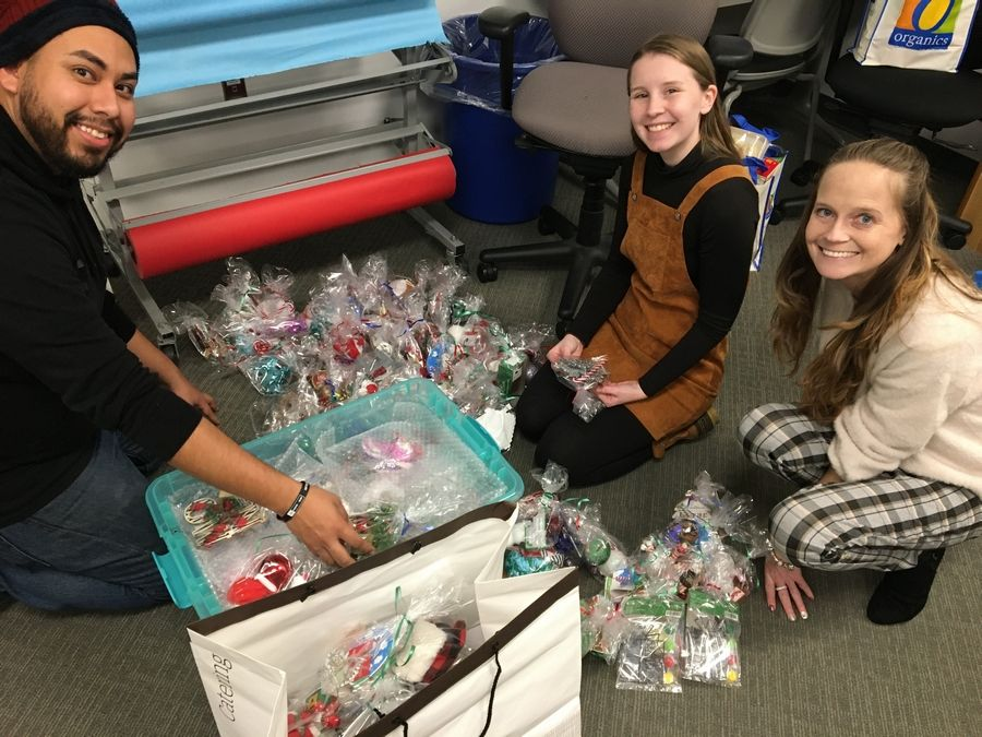 From left, CLC students JuanCarlos Urbina and Colleen Thake help Lyzzi Elliott prepare holiday ornaments for delivery to hospitals and assisted living centers. Elliott founded the nonprofit HOPE Ornaments.
