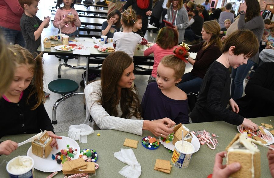 Katie Pietka helps her daughter, Bailey, decorate her gingerbread house Wednesday at Butterfield School in Libertyville.