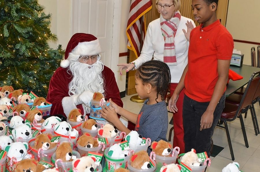 Jayceon Tolson, 5, of Aurora receives a gift from sign-language Santa Dan Basalone of Lisle at Aurora Noon Lions Club's annual yule party Thursday, Dec. 12, for area deaf and hearing-impaired students.