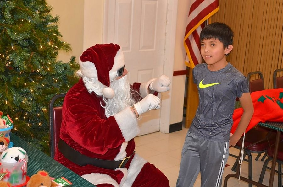 "Sign-language Santa Dan Basalone of Lisle ""talks"" holiday wishes with a student at Aurora Noon Lions Club's annual yule party Thursday, Dec. 12, for area deaf and hearing-impaired students."