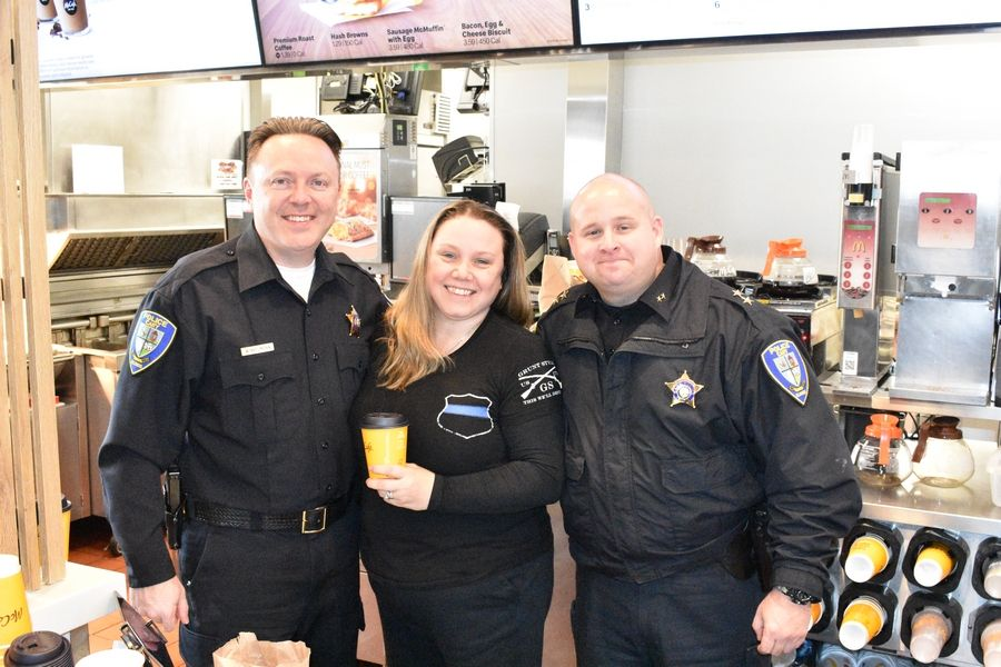 "Cary Deputy Police Chiefs Scott Naydenoff and Chris Winkelmann join Cary resident Marilou Mika at the ""Coffee With A Cop"" event Dec. 18."