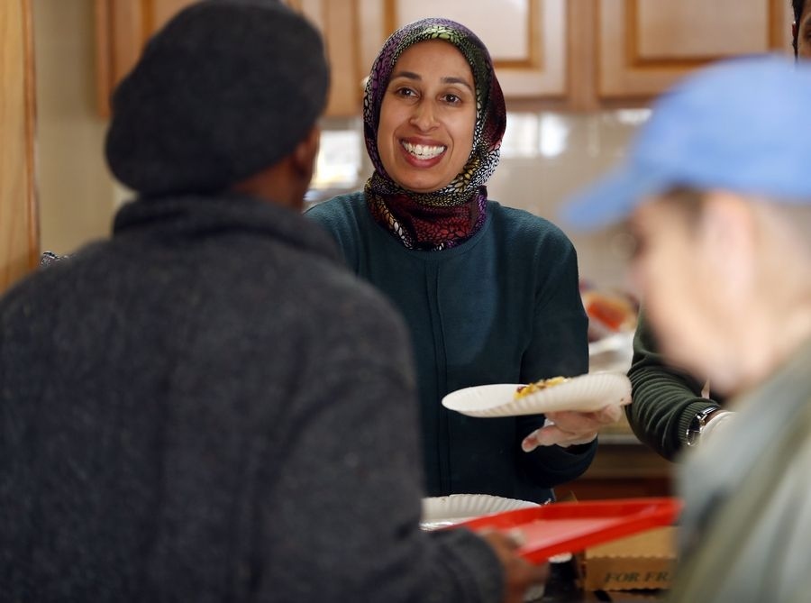 Shazia Khan of South Barrington serves a meal for the homeless Friday at DuPage PADS in Wheaton. She said Muslim and Jewish families who don't celebrate Christmas often feel pressure to participate in the holiday.