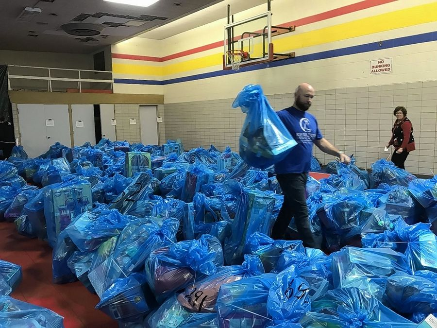 "Volunteer Gus Harshbarger helped distribute bags of toys for the Salvation Army of Elgin's ""Angel Tree"" giveaway program on Saturday."