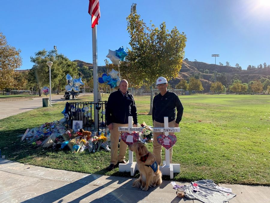 Greg Zanis is joined by Richard Martin, LCC Director of K-9 Ministries, at a memorial for the two victims in a school shooting in Santa Clarita, California.