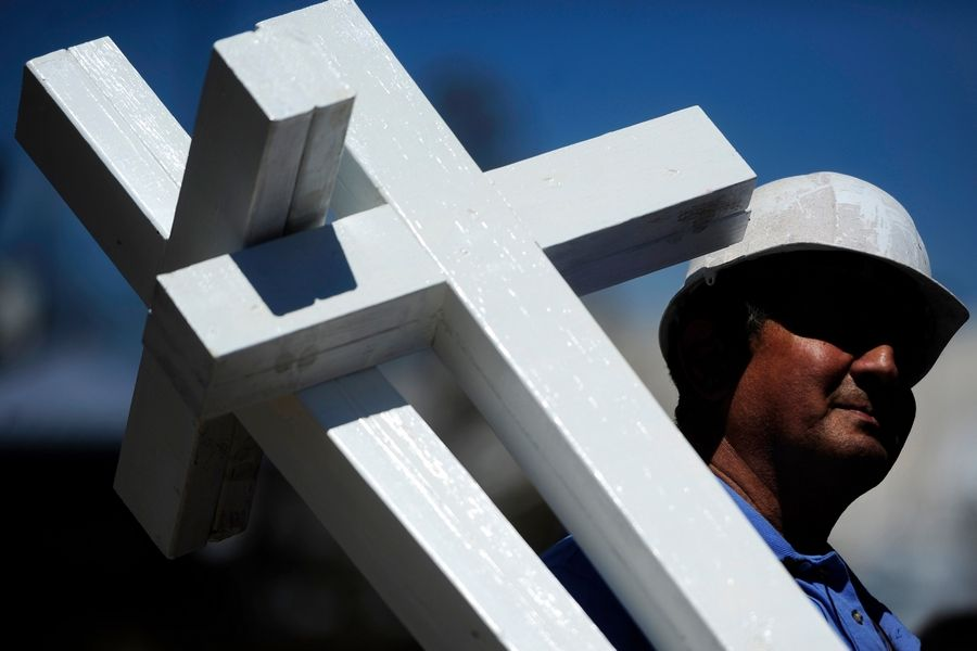 "Greg Zanis, of Aurora, carries crosses for a memorial for the victims of the theater shooting on Sunday, July 22, 2012, in Aurora, Colorado. Twelve were killed and 58 were wounded when suspected gunman James Holmes opened fire on a crowd during a late night screening of ""The Dark Knight Rises."""