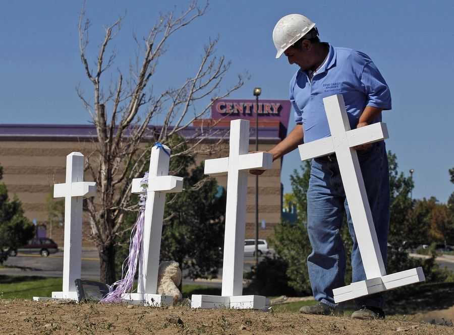 "Greg Zanis, from Aurora, Ill., places 12 crosses, one for each victim, across the street from the Century 16 movie theater in Aurora, Colo. on Sunday, July 22, 2012. Twelve people were killed and dozens injured in a shooting attack early Friday at the packed theater during a showing of the Batman movie, ""The Dark Knight Rises."" Police have identified the suspected shooter as James Holmes, 24. in 1999, Zanis placed 15 crosses near Columbine High School to commemorate the victims."