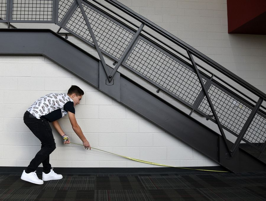 Sophomore Gabriel Majocha measures a wall during a review for finals in his geometry in construction class that's part of the career and technical education program at Huntley High School. Students were measuring the area to calculate how much material would be needed in certain construction projects.