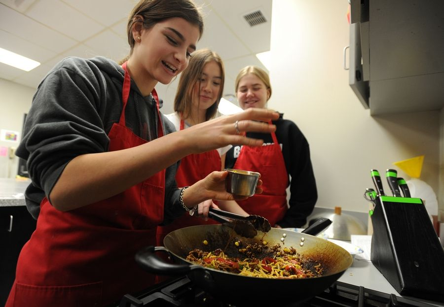 Caroline Colella, 16, with Parah Muldoon, 15, and Emma Paulson, 16, prepare food in a culinary arts class at Barrington High School. The course is part of Barrington High's career and technical education program.