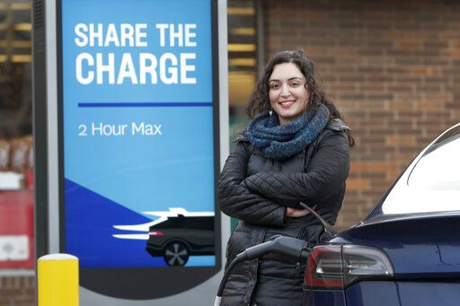 "In this Friday, Dec. 20, 2019, photo, Neda Deylami poses for a portrait while charging her electric vehicle at a Chicago area grocery store. Owners of electric vehicles in a number of states will start seeing fees to pay for road repairs in the new year. At least eight states will begin charging new or higher registration fees Wednesday, Dec. 25, for electric vehicles or plug-in hybrids. ""It's kind of a blanket penalty for anyone who chooses to go electric,"" said Deylami, a Tesla owner who founded Chicago for EVs, a group that advocates for electric vehicles."