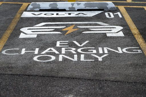 In this Friday, Dec. 20, 2019, photo shows a designated parking space for electric vehicles at a Chicago area grocery store. Owners of electric vehicles in a number of states will start seeing fees to pay for road repairs in the new year. At least eight states will begin charging new or higher registration fees Wednesday, Dec. 25, for electric vehicles or plug-in hybrids.
