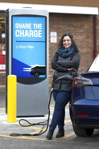 "In this Friday, Dec. 20, 2019, photo Neda Deylami poses for a portrait while charging her electric vehicle at a Chicago area grocery store. Owners of electric vehicles in a number of states will start seeing fees to pay for road repairs in the new year. At least eight states will begin charging new or higher registration fees Wednesday, Dec. 25, for electric vehicles or plug-in hybrids. ""It's kind of a blanket penalty for anyone who chooses to go electric,"" said Deylami, a Tesla owner who founded Chicago for EVs, a group that advocates for electric vehicles."