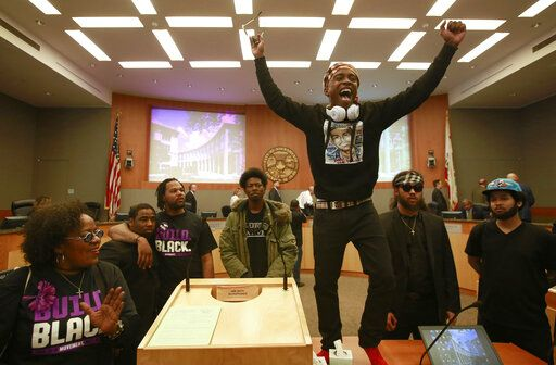 FILE - In this March 27, 2018, file photo Stevante Clark stands on a desk as he shouts the name of his brother Stephon Clark, who was fatally shot by police a week earlier, during a meeting of the Sacramento City Council, in Sacramento, Calif. The shooting death of Stephon Clark helped spur the passage of two laws to take effect in 2020 giving California one of the nation's most comprehensive approaches to deterring shootings by police.