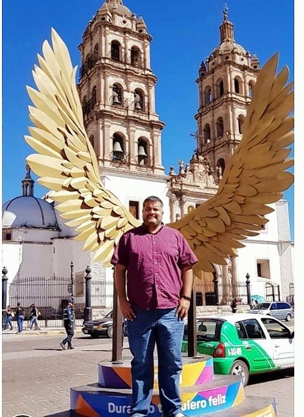 The Rev. Manuel Gomez stands in front of a sculpture of wings during a visit to his hometown in Durango, Mexico, a few years ago. Gomez, 36, died Thursday after battling cancer for the past month.