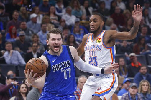 Dallas Mavericks forward Luka Doncic (77) drives past Oklahoma City Thunder guard Terrance Ferguson (23) during the first half of an NBA basketball game Tuesday, Dec. 31, 2019, in Oklahoma City.