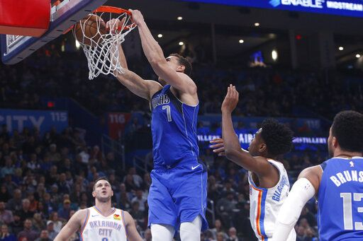 Dallas Mavericks forward Dwight Powell (7) dunks between Oklahoma City Thunder forward Danilo Gallinari, left, and guard Shai Gilgeous-Alexander during the first half of an NBA basketball game Tuesday, Dec. 31, 2019, in Oklahoma City.