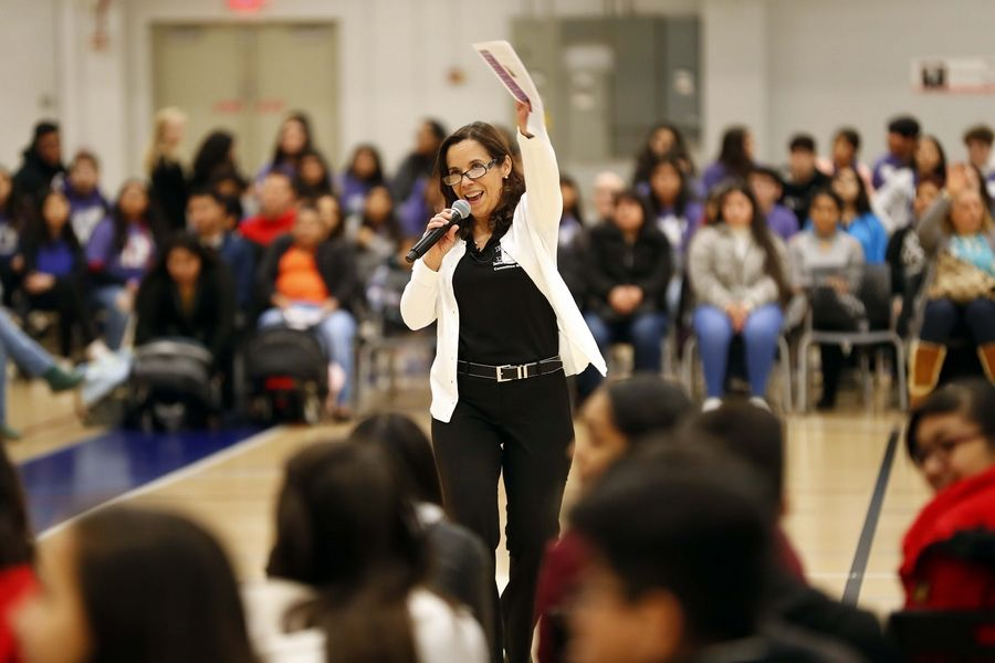 Claudia Rueda-Alvarez gets students excited at Harper College's Latino Summit in Palatine. Community colleges are trying a variety of tactics to attract and retain minority students and help them be successful.